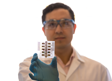 Julian Lamanna holds the digital microfluidic chip designed for the MR Boxes.